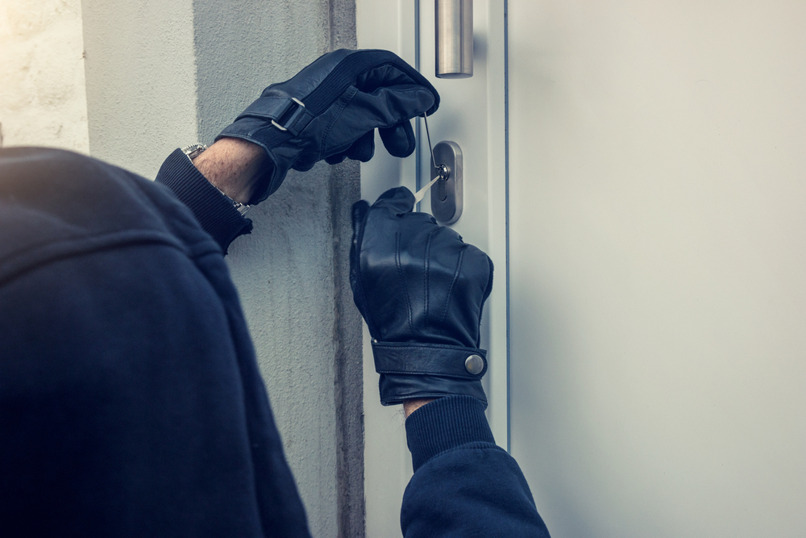 unsolved burglaries burglar picking a lock on a house